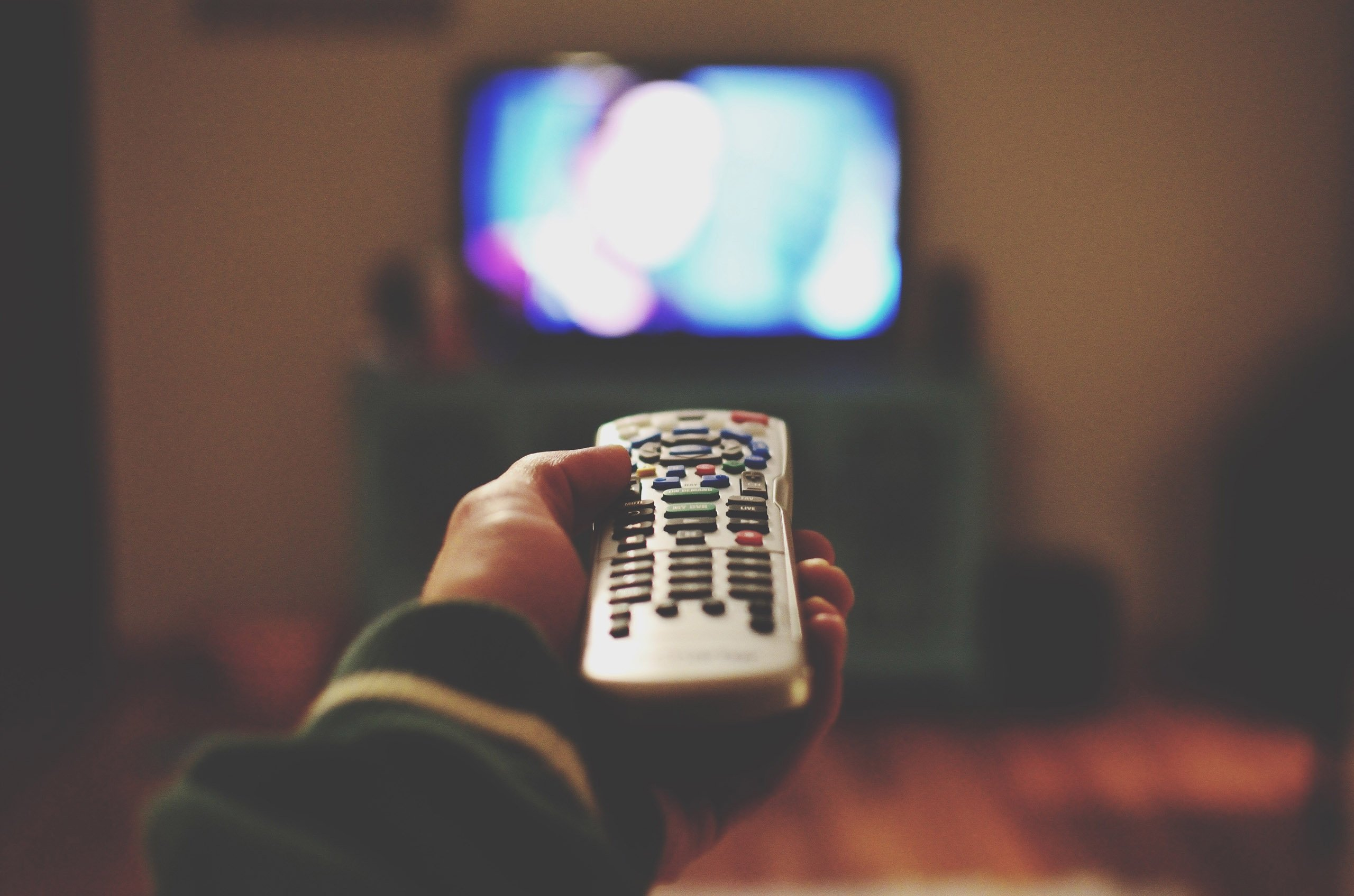 Cropped Of Person Holding Remote Control Against Television Set At Home